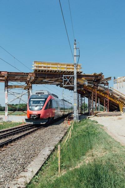 Passenger train passes under the becoming bridge
