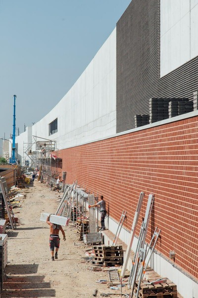 Brick wall with heavy dragging construction worker