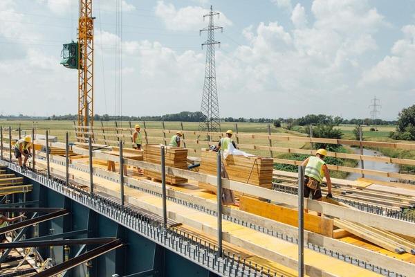 Construction workers work on the progressive overpass