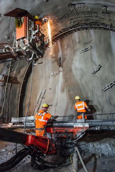 Bauarbeiter machen unterschiedliche Tätigkeiten im Tunnel