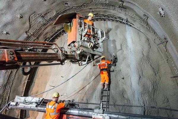 Bauarbeiter bereiten Tunnelwand auf Sprengung vor