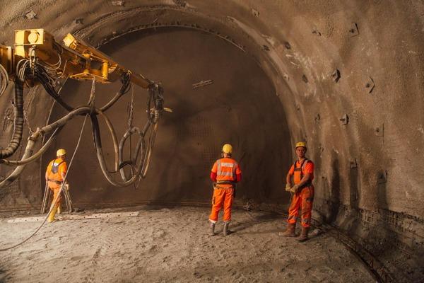 Kranbohrer bohrt in die Tunnelwand mit Bauarbeiter