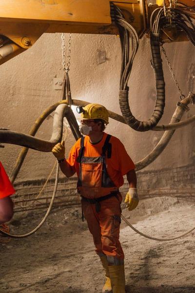 Bauarbeiter mit Maske und Helm vor Kranbohrer