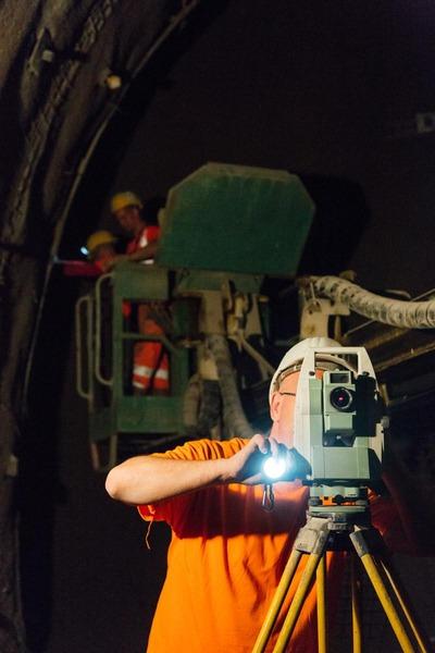 Bauarbeiter macht Vermessungsarbeiten mit Arbeitern auf der Hebebühne im Hintergrund