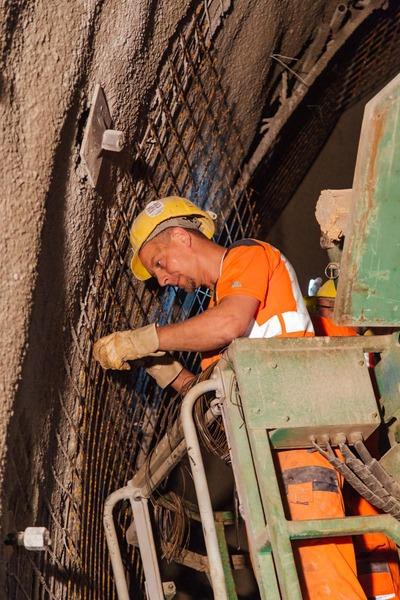 Bauarbeiter auf Hebebühne arbeitet am Tunnelgitter
