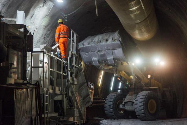 Bauarbeiter auf einer Maschine, der dem Baggerfahrer Anweisungen gibt
