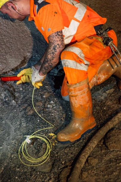 Bauarbeiter tätigt Verdrahtungen mit Sprengstoff an der Tunnelwand