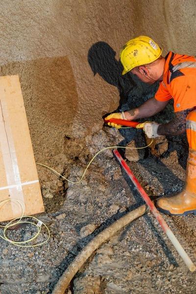 Bauarbeiter gibt Sprengstoff in die Tunnelwandlöcher