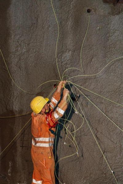 Bauarbeiter verbindet alle Drähte, die an der Tunnelwand sind