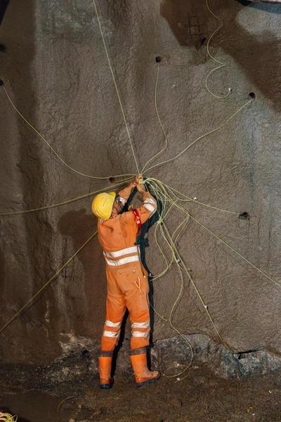 Bauarbeiter verknotet alle Drähte, die an der Tunnelwand sind