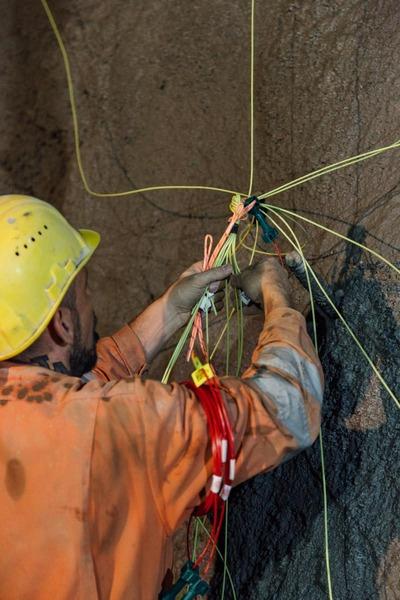 Bauarbeiter macht weitere Arbeitsschritte mit den verbundenen Drähte an der Tunnelwand