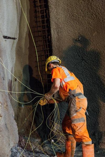 Anderer Bauarbeiter verbindet alle Drähte an der Tunnelwand
