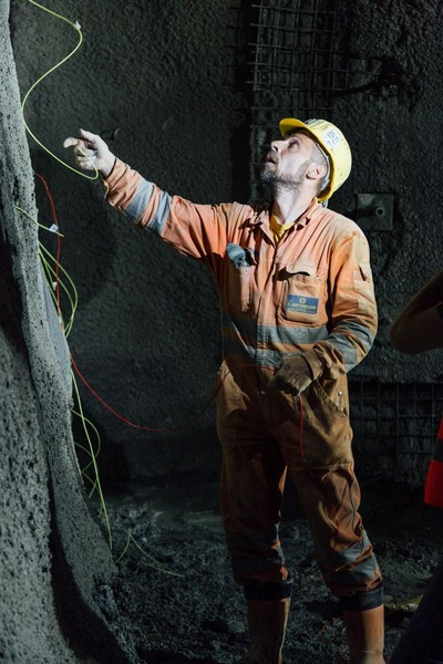 Bauarbeiter schaut sich die Drähte an der Tunnelwand an
