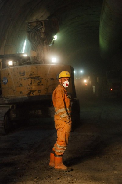 Bauarbeiter mit Maske und Helm im Tunnel