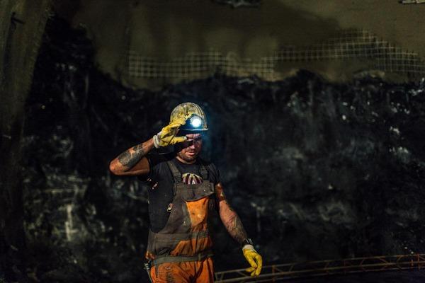 Schmutziger Bauarbeiter mit Helm und Licht