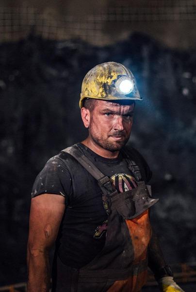 Konzentrierter, schmutziger Bauarbeiter