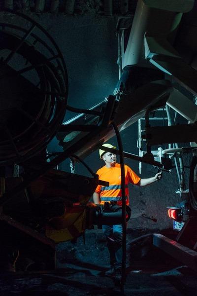 Bauarbeiter im dunklen Tunnel mit Maschine