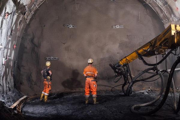 Bauarbeiter stehen vor Tunnelwand mit Tunnelbohrer