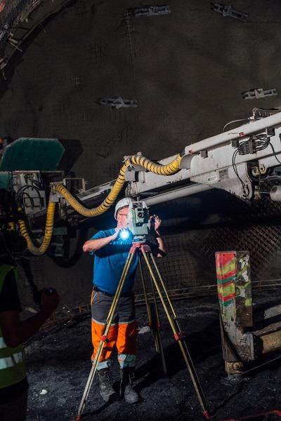 Bauarbeiter tätigt Bemessungen im Tunnel