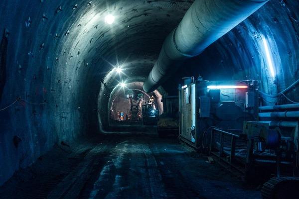 Fernblick in den dunklen Tunnel mit Bauarbeitern und Maschinen im Hintergrund