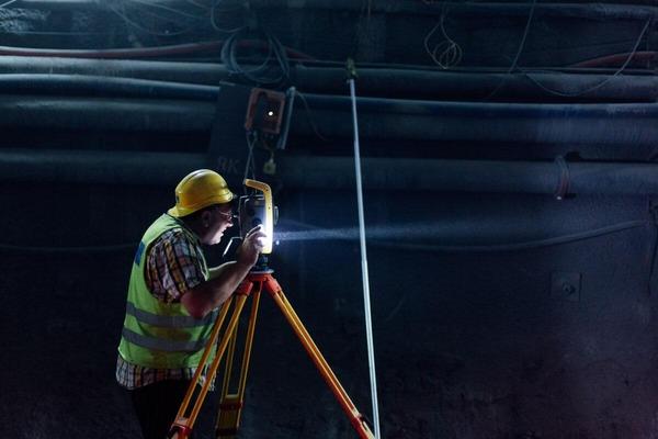Bauarbeiter tätigt Bemessungen im dunklen Tunnel