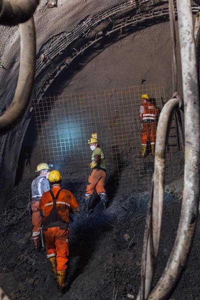 Bauarbeiter arbeiten an der Tunnelwand und besprechen die Lage