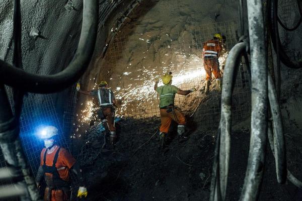 Bauarbeiter führt Schweißarbeiten durch und andere Bauarbeiter beaufsichtigen ihn dabei