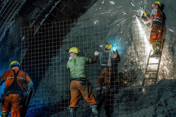 Bauarbetier arbeiten zusammen an der Tunnelwand