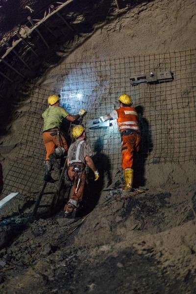 Bauarbeiter befestigten ein Gitter an der Tunnelwand