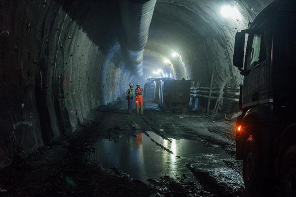 Blick in den dunklen Tunnel, wo sich zwei Bauarbeiter unterhalten