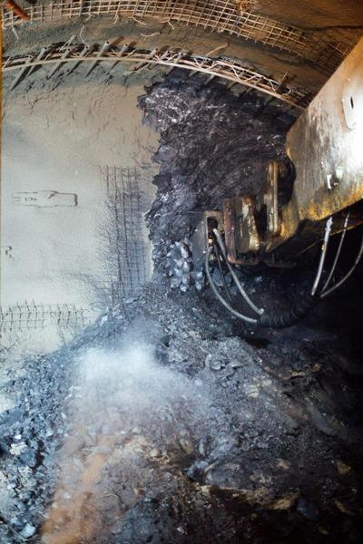 Tunnelbohrer bohrt in die Tunnelwand, Gestein bricht heraus