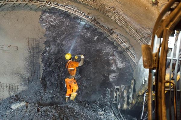Bauarbeiter bemisst die ausgebohrte Tunnelwand