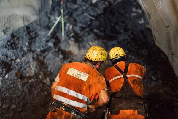 Bauarbeiter begutachten gemeinsam das ausgebrochene Gestein