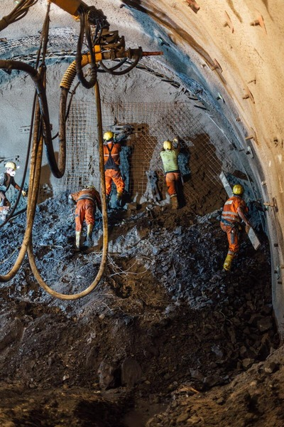 Bauarbeiter haftieren ein Gitter auf die bearbeitete Tunnelwand