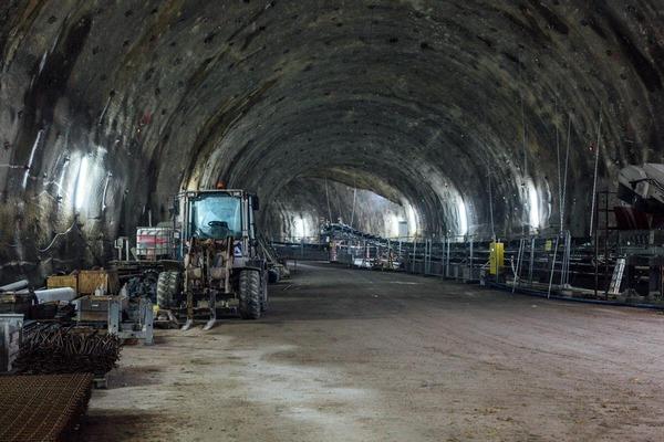 Blick in den Tunnel mit Bagger und Baumaterial