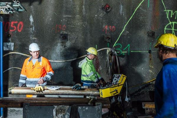 Bauarbeiter und im Hintergrund Tunnelwand mit Beschriftungen