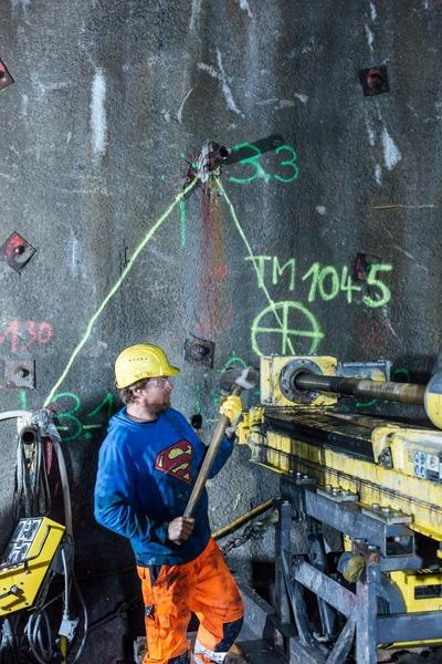 Bauarbeiter mit Hammer bei einer Maschine
