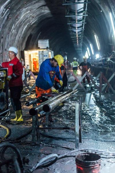 Bauarbeiter sägt an einer Röhre im Tunnel