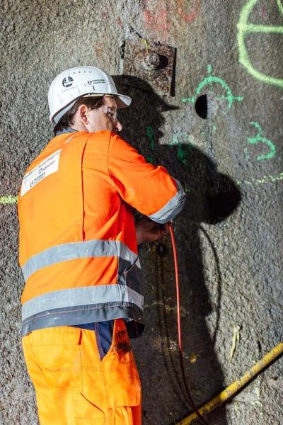 Bauarbeiter arbeitet bei der Tunnelwand