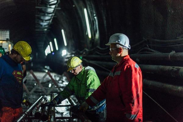 Drei Bauarbeiter arbeiten an Röhren