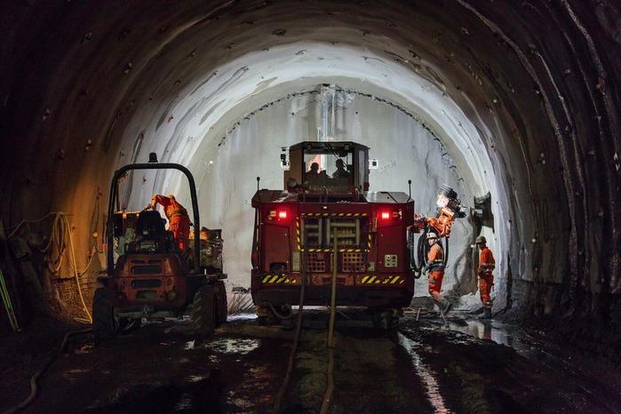 Baumaschine und Bauarbeiter arbeiten an der Tunnelwand