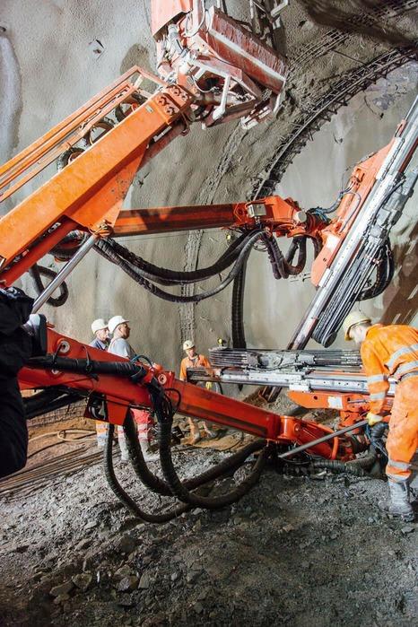 Bauarbeiter und Baumaschine arbeiten an der Tunnelwand