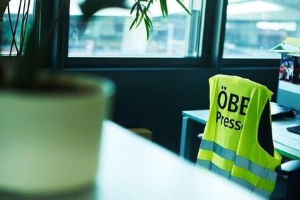 """Aufnahme im Büro gemacht eines Arbeitsplatzes. Eine Warnweste hängt über einem Bürostuhl und darauf steht """"ÖBB Presse""""."""
