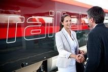Frau und Mann in Businesskleidung stehen am Bahnsteig und schütteln Hände. Im Hintergrund steht ein Railjet.