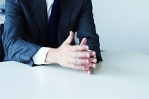 Business-Mann am Schreibtisch, der redet. Man sieht nicht seinen Kopf, nur den Oberkörper und die Hände stehen im Mittelpunkt.