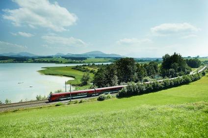 Railjet fährt neben See vorbei