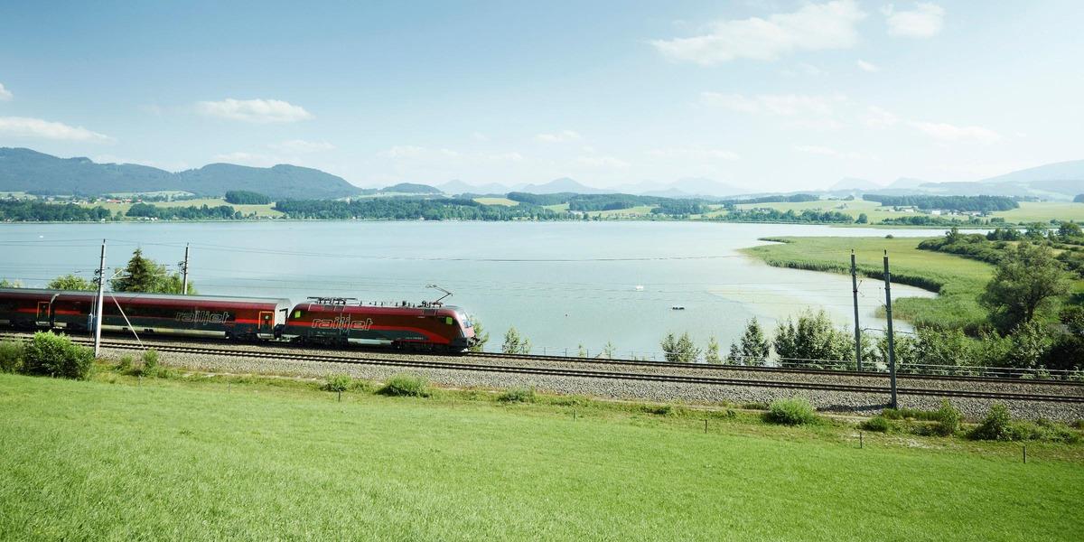 Zug in Landschaft, See dahinter