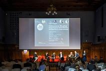 """Eine Bühne mit einer großen Leinwand im Hintergrund mit Beteiligten von der Veranstaltung zur Podiumsdiskussion """"Fit4Generations. Wie gelingt ausgewogenes Generationsmanament in Unternehmen"""""""