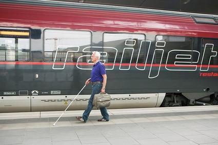 Sehbehindeter älterer Herr mit Blindenstock läuft am taktilen Leitsystem am Bahnsteig entlang. In der linken Hand hält er einen Koffer. Im Hintergrund steht ein Railjet.