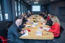 TeilnehmerInnen sitzen am grossen Tisch und diskutieren